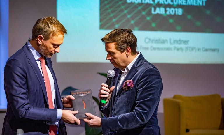 """Sven Marlinghaus presents Christian Lindner with Roland Berger's latest book """"Re-entrepreneuring""""."""