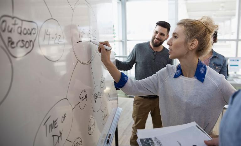 woman writing on whiteboard at work