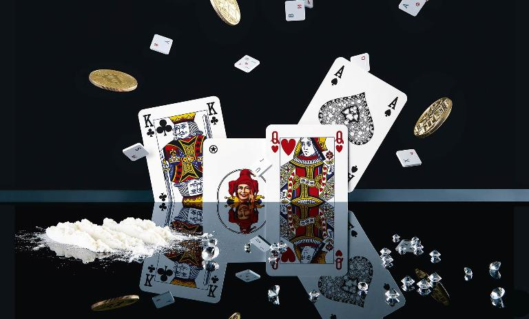 Playing cards, loose keyboard buttons and gold coins with the Bitcoin logo scatter upwards and are reflected in a high-gloss table on which a pile of white powder sits next to diamonds, symbolizing the spread of digital crime