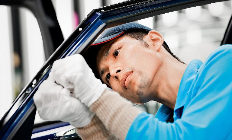 Handcrafted: A Toyota employee assembles a door window frame on the Mirai vehicle without robotic assistance.