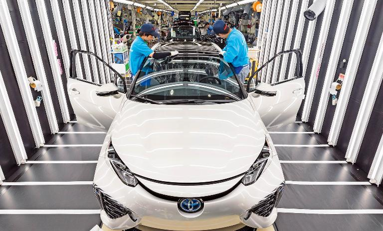 Two workers at Toyota's Motomachi Plant inspect a Mirai model car