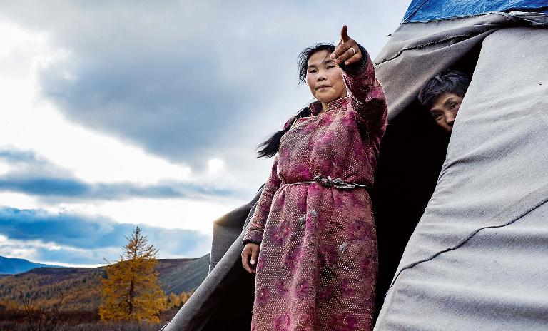 A young female member of the Mongolian Tsaatan reindeer shepherd tribe stands outside of her teepee with her husband behind her