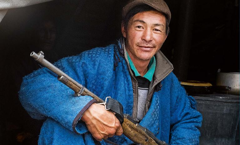 A male member of the Mongolian Tsaatan reindeer shepherd tribe sits with his hunting gun