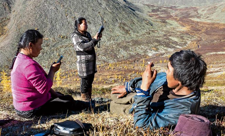 Members of the Mongolian Tsaatan reindeer shepherd tribe stand on high ground with mobile devices looking for a signal