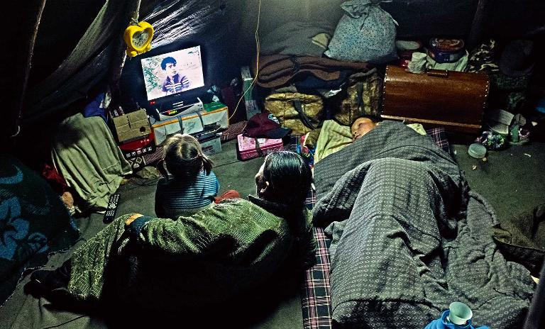 A child and two adult members of the Mongolian Tsaatan reindeer shepherd tribe watch TV inside of a teepee