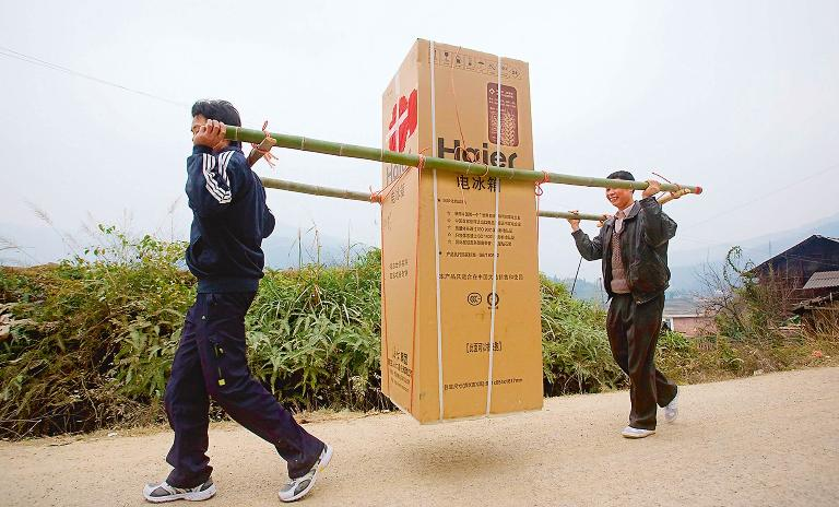 A global innovator: Chinese farmers carry a Haier refrigerator on their way back to their village in Anhui.